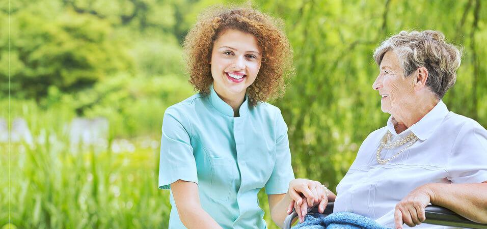 senior woman and nurse smiling