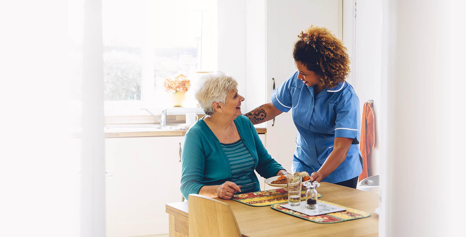 elder woman eating, accompanied by a nurse